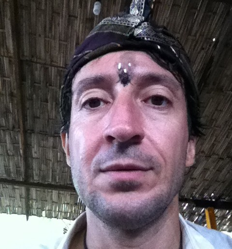 Thomas wearing a traditional hat and a puja