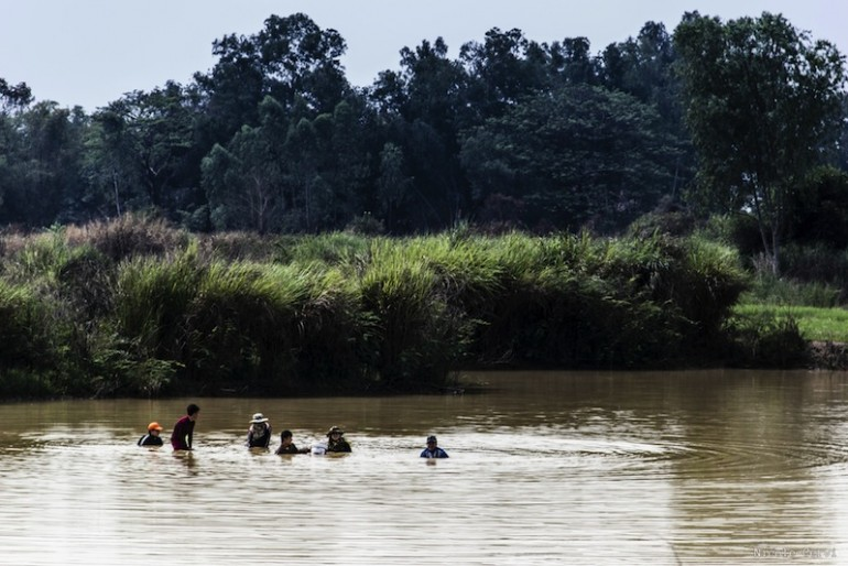 people with half their body submerged - searching with their hands in the river bottom