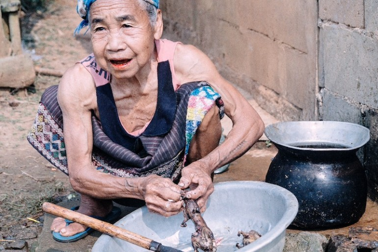 Old woman skinning a squirrel