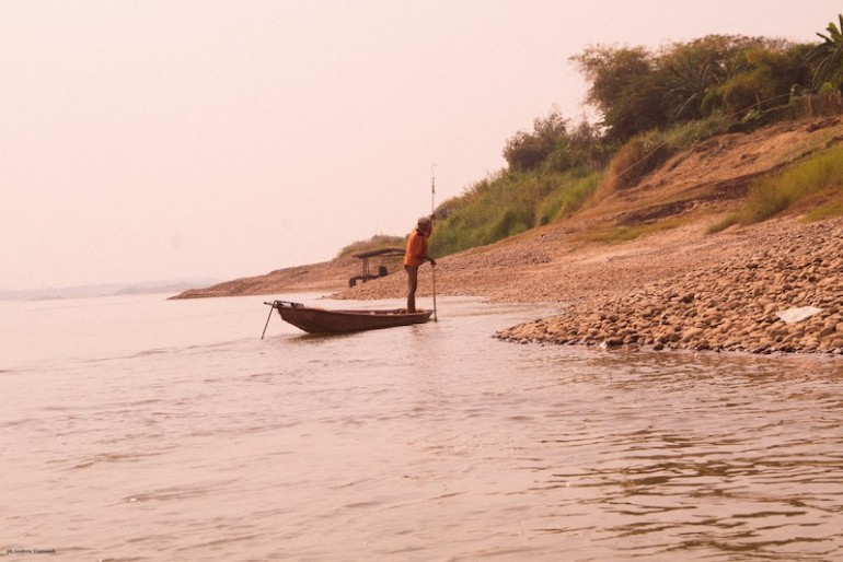 a fisherman balancing and propelling a long and lean wooden boat with an elongated bamboo sticks