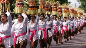 Women carrying fruit offerings piled four feet tall on their heads