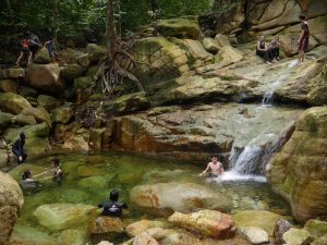 People swimming and soaking at the Satubong Waterfall