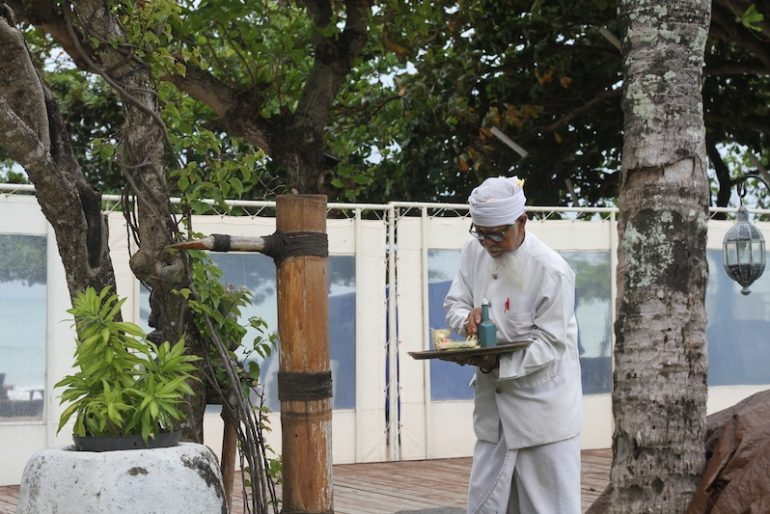 Priest performing offerings in the hotel gardens