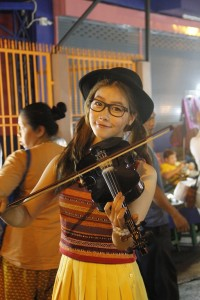 A young violin player performing in Walai Road