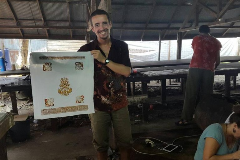 A proud tourist shows his own batik production