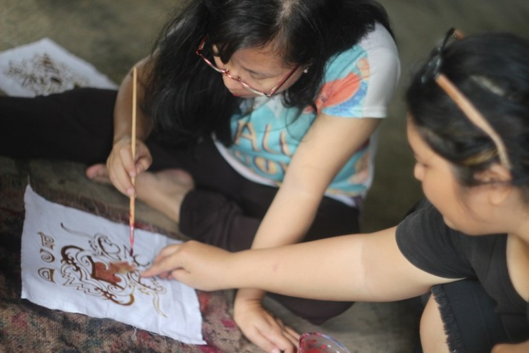 A visitor trying her skills at batik making