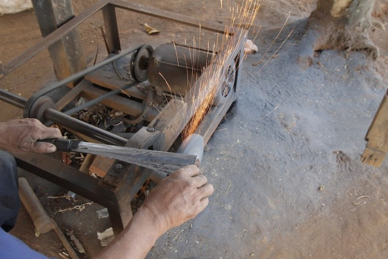 Male making a knife' blade at blacksmith village