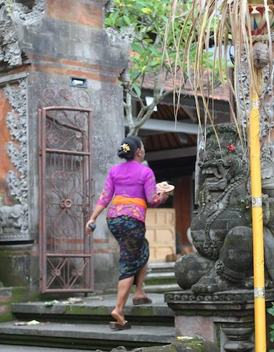 Woman entering a Ubud temple for ceremony offerings