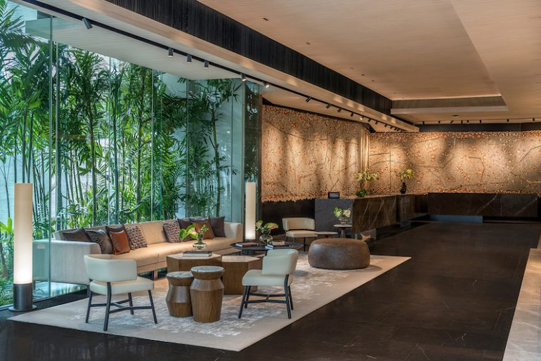 An urban oasis with a contemporary reception welcoming guests with warm DoubleTree Cookies and Creating A Rewarding Experience (CARE) service culture