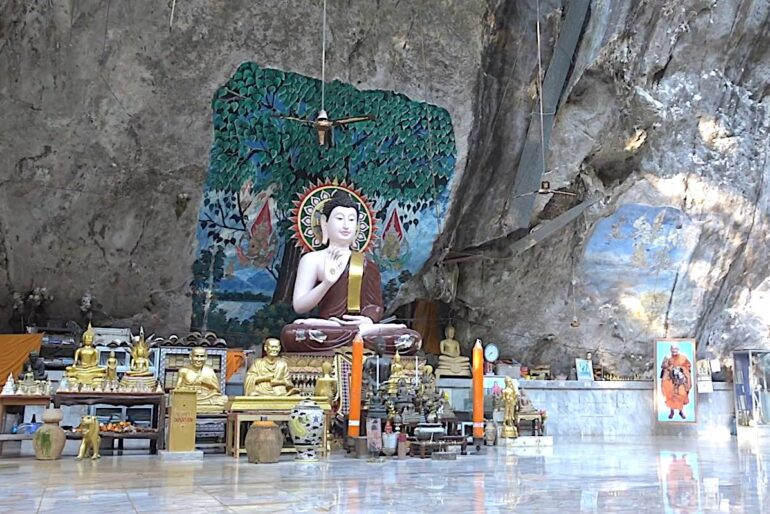 Big Buddha statue and other Buddha images are set against the karst wall and fronted by a gleaming marble floor